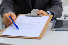Бизнесмен при контракт давая ручку к партнеру для того чтобы подписать ее Стоковые Фотографии RF
