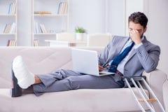 Бизнесмен при костыли и сломанная нога дома работая Стоковое Изображение
