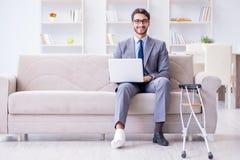Бизнесмен при костыли и сломанная нога дома работая Стоковые Фотографии RF