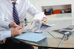 Бизнесмен при коллега обсуждая обработку документов стоковое фото
