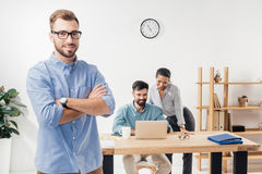 Бизнесмен при пересеченные оружия стоя в работе офиса и коллег Стоковые Фотографии RF