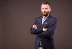 Бизнесмен при пересеченные руки стоя на серой предпосылке стоковая фотография