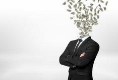 Бизнесмен при перехоженные вброд руки и много долларовых банкнот летая вне вместо его головы Стоковая Фотография