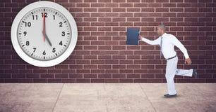 Бизнесмен при портфель бежать поздно с часами установил на стене Стоковая Фотография RF