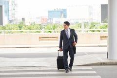 Бизнесмен при чемодан идя к авиапорту Стоковые Фото