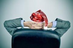 Бизнесмен при шляпа santa ослабляя в его стуле офиса Стоковое фото RF