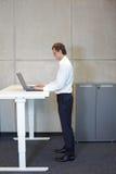 Бизнесмен при eyeglasses стоя на таблице установки высоты Стоковое Изображение