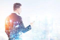 Бизнесмен при smartphone смотря город Стоковое Изображение