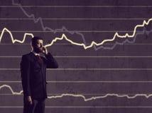 Бизнесмен при smartphone стоя над предпосылкой диаграммы Бушель Стоковые Фото