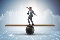 Бизнесмен пробуя сбалансировать на шарике и seesaw Стоковая Фотография RF