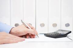 Бизнесмен проверяет финансовые номера в контракте Стоковая Фотография RF