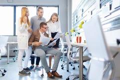 Бизнесмен проверяя бумаги с его членами компании на предпосылке офиса доллар принципиальной схемы удя крытую работу взгляда накло стоковая фотография rf