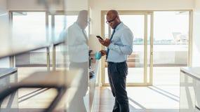 Бизнесмен проверяя мобильный телефон пока имеющ завтрак Стоковые Изображения RF