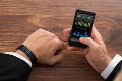 Бизнесмен проверяя stats фитнеса на мобильном телефоне Стоковое Изображение