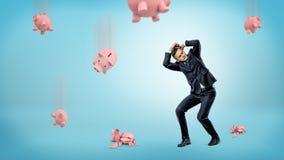Бизнесмен прячет его голову от много копилок которые падают вниз и трескают на поле Стоковое Изображение