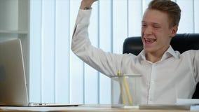 Бизнесмен работает в офисе и деньги падают на его движение медленное акции видеоматериалы