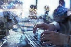 Бизнесмен работает в офисе с компьтер-книжкой на переднем плане Концепция сыгранности и партнерства двойная экспозиция с стоковое изображение