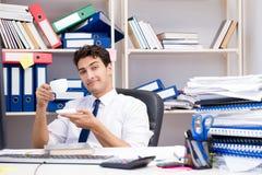 Бизнесмен работая в офисе с кучами книг и бумаг Стоковая Фотография RF