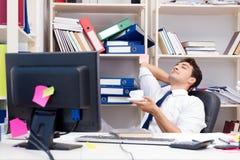 Бизнесмен работая в офисе с кучами книг и бумаг Стоковое фото RF