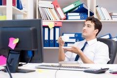 Бизнесмен работая в офисе с кучами книг и бумаг Стоковые Изображения RF