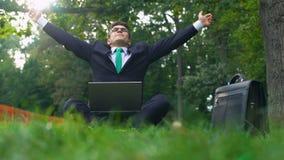 Бизнесмен работая в парке принимая остатки и бросая руки до неба, релаксацию сток-видео