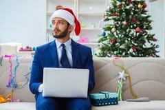 Бизнесмен работая дома во время рождества Стоковое Фото