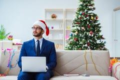 Бизнесмен работая дома во время рождества Стоковые Изображения