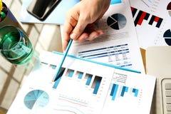 Бизнесмен работая и анализируя финансовые диаграммы на диаграммы на компьтер-книжке Стоковое Изображение RF