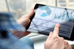 Бизнесмен работая и анализируя финансовые диаграммы на диаграммы на компьтер-книжке в офисе Стоковая Фотография