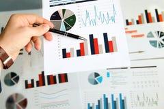 Бизнесмен работая и анализируя финансовые диаграммы на диаграммы Стоковые Фото