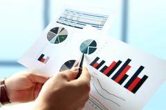 Бизнесмен работая и анализируя финансовые диаграммы на диаграммы Стоковое фото RF