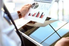 Бизнесмен работая и анализируя финансовые диаграммы на диаграммы Стоковые Изображения