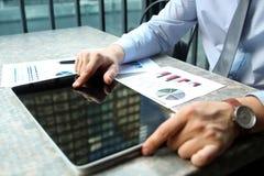 Бизнесмен работая и анализируя финансовые диаграммы на диаграммы на компьтер-книжке снаружи Стоковые Изображения RF