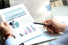 Бизнесмен работая и анализируя финансовые диаграммы на диаграммы на компьтер-книжке снаружи Стоковые Фото