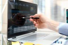 Бизнесмен работая и анализируя финансовые диаграммы на диаграммы используя компьтер-книжку Стоковые Изображения RF