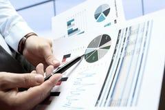 Бизнесмен работая и анализируя финансовые диаграммы на диаграммы Стоковые Фотографии RF