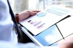 Бизнесмен работая и анализируя финансовые диаграммы на диаграммы используя компьтер-книжку Стоковые Изображения