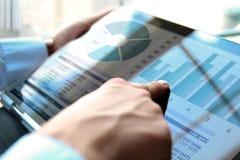 Бизнесмен работая и анализируя финансовые диаграммы на диаграммы используя компьтер-книжку Стоковая Фотография