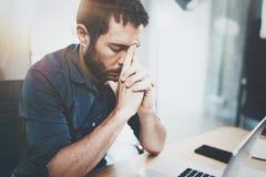 Бизнесмен работая на деревянном столе на современном офисе просторной квартиры Стул задумчивого человека сидя и использование сов Стоковое Фото