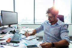 Бизнесмен работая на его столе в офисе Стоковая Фотография RF