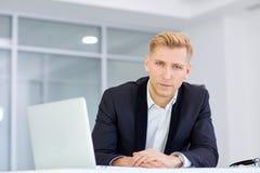 Бизнесмен работая на его столе с компьтер-книжкой в офисе стоковая фотография rf