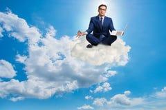 Бизнесмен работая на компьтер-книжке в небе Стоковые Фото