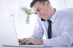 Бизнесмен работая на компьтер-книжке в офисе Стоковые Изображения