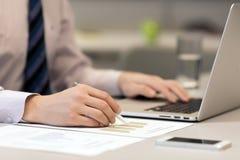 Бизнесмен работая на компьтер-книжке и напечатанных диаграммах Стоковое Фото