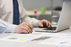 Бизнесмен работая на компьтер-книжке и напечатанных диаграммах Стоковая Фотография