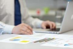Бизнесмен работая на компьтер-книжке и напечатанных диаграммах Стоковые Фотографии RF