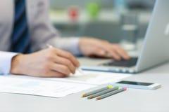 Бизнесмен работая на компьтер-книжке и напечатанных диаграммах Стоковое фото RF
