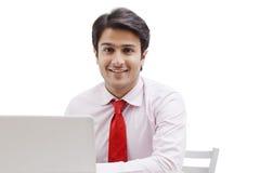 Бизнесмен работая на компьтер-книжке и усмехаться Стоковая Фотография RF