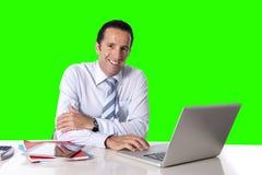 Бизнесмен работая на компьтер-книжке компьютера сидя на ключе chroma стола офиса стоковая фотография rf