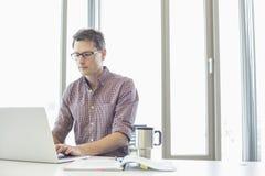 Бизнесмен работая на компьтер-книжке на столе в творческом офисе Стоковые Фотографии RF